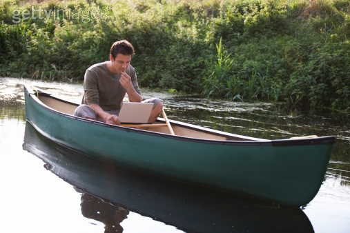 Royalty-free Image: Young man sitting in a boat working on…